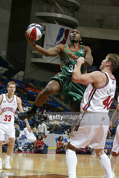 Roland Roberts of the Charleston Lowgators drives past Jason Collier of the Fayetteville Patriots at the Crown Coliseum November 29 2003 in North...