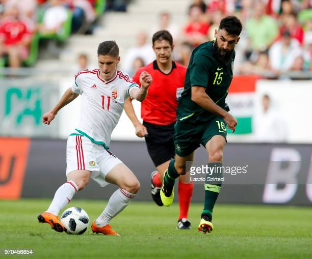 Roland Sallai of Hungary shoots on goal next to Aziz Behich of Australia in front of referee Matej Vidali during the International Friendly match...