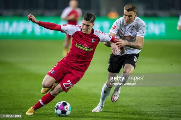 Roland Sallai of SC Freiburg and Louis Jordan Beyer of Borussia Moenchengladbach battle for the ball during the Bundesliga match between Borussia...