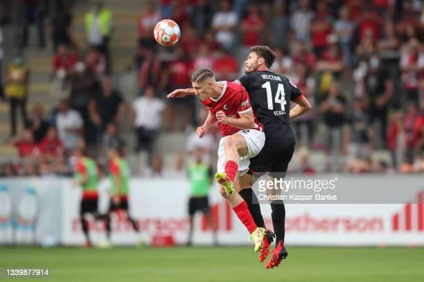 Roland Sallai of SC Freiburg challenges Jonas Hector of 1.FC Koeln during the Bundesliga match between Sport-Club Freiburg and 1. FC Köln at...