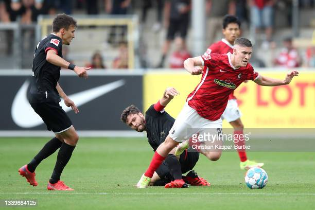 Roland Sallai of SC Freiburg is challenged by Jonas Hector of 1.FC Koeln during the Bundesliga match between Sport-Club Freiburg and 1. FC Köln at...