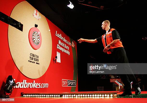 Roland Scholten of The Netherlands throws against Dave Whitcombe of Great Britain during the Ladbrokes World Darts Championship at The Circus Tavern...