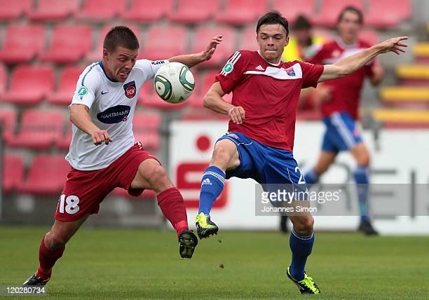Roland Sternisko of Unterhaching battles for the ball with Bastian Heidenfelder of Heidenheim during the Third League match between SpVgg...