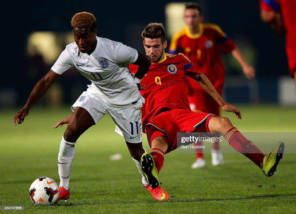 Rolando Aarons of Engand holds off pressure from Alexandru Tudorie of Romania during the U20 International friendly match between England and Romania on September 5, 2014 in Telford, England.