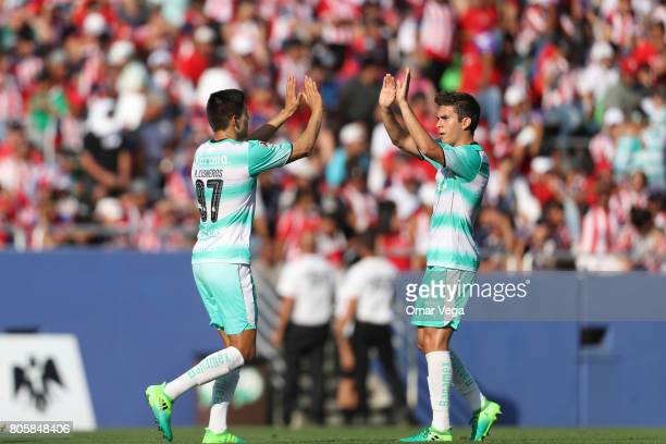 Rolando Cisneros of Santos Laguna celebrates with teammate Ulises Rivas after scoring the third goal of his team during the friendly match between...