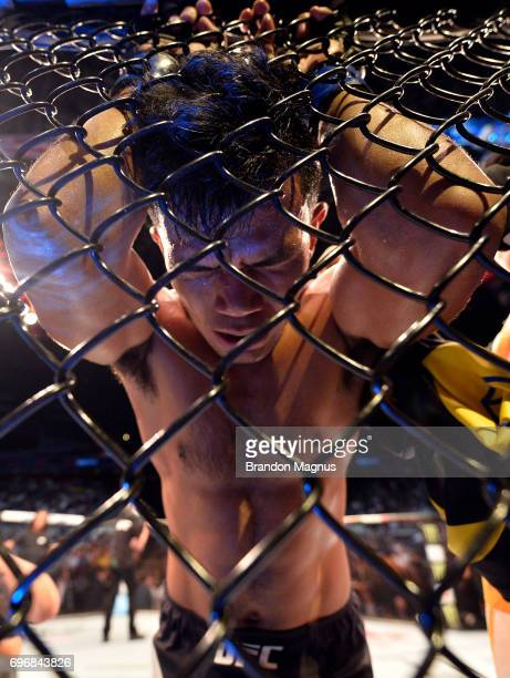 Rolando Dy of the Philippines reacts after his TKO loss to Alex Caceres in their featherweight bout during the UFC Fight Night event at the Singapore...