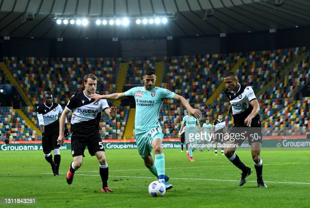 Rolando Mandragora of Torino FC is challenged by Thomas Ouwejan and Rodrigo Becao during the Serie A match between Udinese Calcio and Torino FC at...