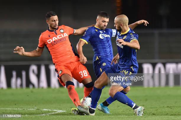 Rolando Mandragora of Udinese is challenged by Miguel Veloso and Sofyan Amrabat of Hellas Verona during the Serie A match between Hellas Verona and...
