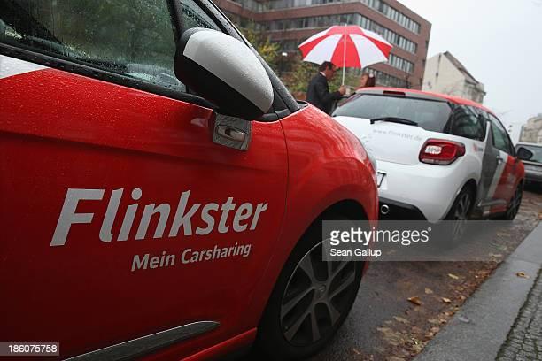 Rolf Luebke Chairman of Deutsche Bahn Mobility Networks Logistics which owns carsharing provider Flinkster shows Elena Eybe Flinkster's 250000th...