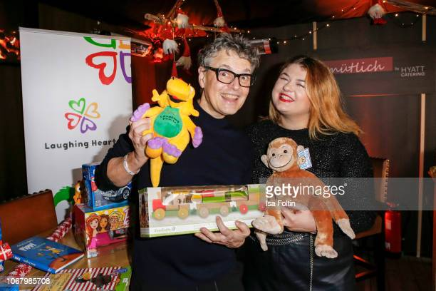 Rolf Scheider and German singer Alina Wichmann alias Alina wrap a present for children in need during the Laughing Hearts Charity Christmas event at...