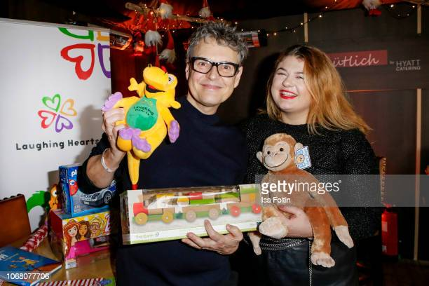 Rolf Scheider and German singer Alina Wichmann alias Alina wrap presents for children in need during the Laughing Hearts Charity Christmas event at...