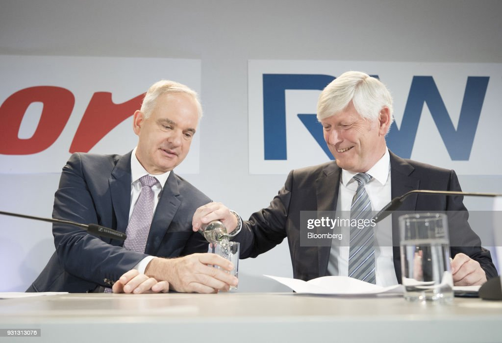 Rolf Schmitz, chief executive officer of RWE AG, right, pours a glass of water for Johannes Teyssen, chief executive officer of EON SE, during a news conference in Essen, Germany, on Tuesday, March 13, 2018. EON will shed as many as 5,000 jobs in the deal to take over Innogy SE, a move that marks the biggest shakeup in Germany's energy business in years. Photographer: Jasper Juinen/Bloomberg via Getty Images