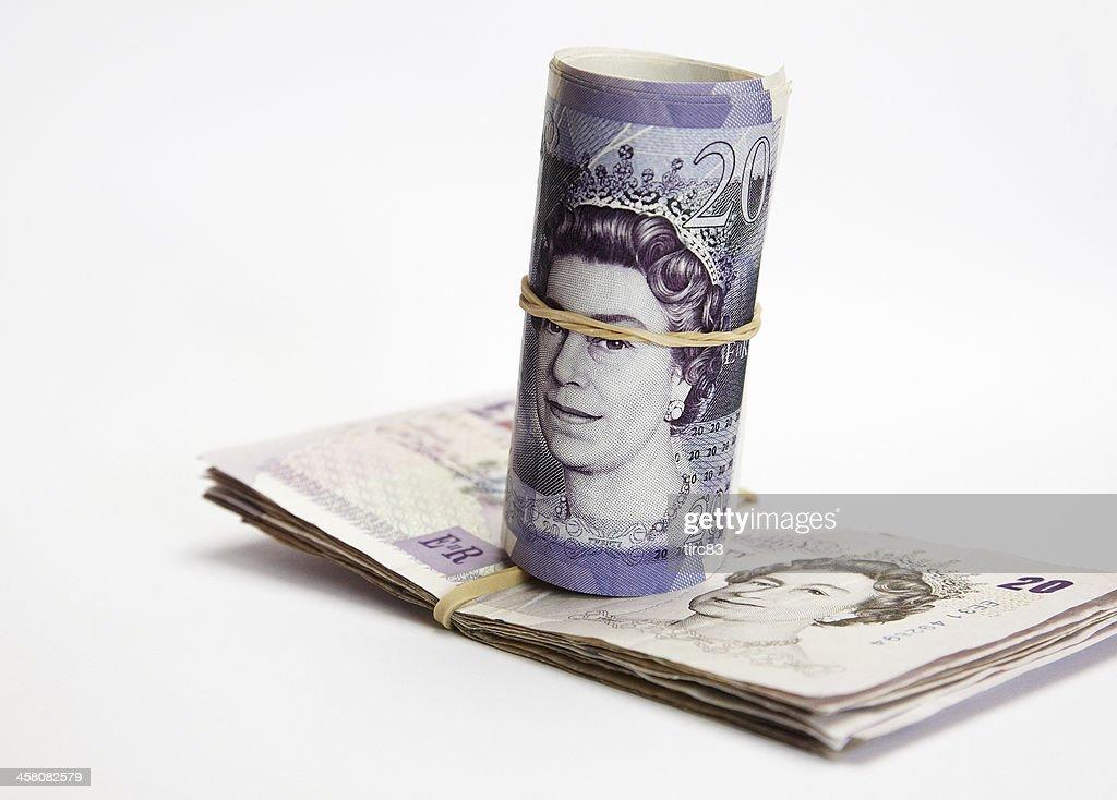 Roll and wad British twenty pound notes : Stock Photo