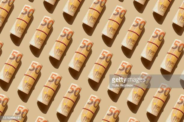 roll of 50 euro banknotes on the beige background - european union currency stock pictures, royalty-free photos & images