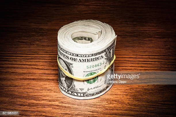 Roll of american dollar notes wrapped in elastic band on office desk