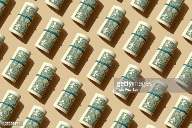 roll of american dollars banknotes on the beige background - geld stock-fotos und bilder