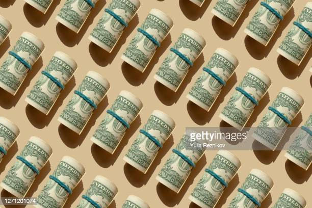roll of american dollars banknotes on the beige background - us paper currency stock pictures, royalty-free photos & images