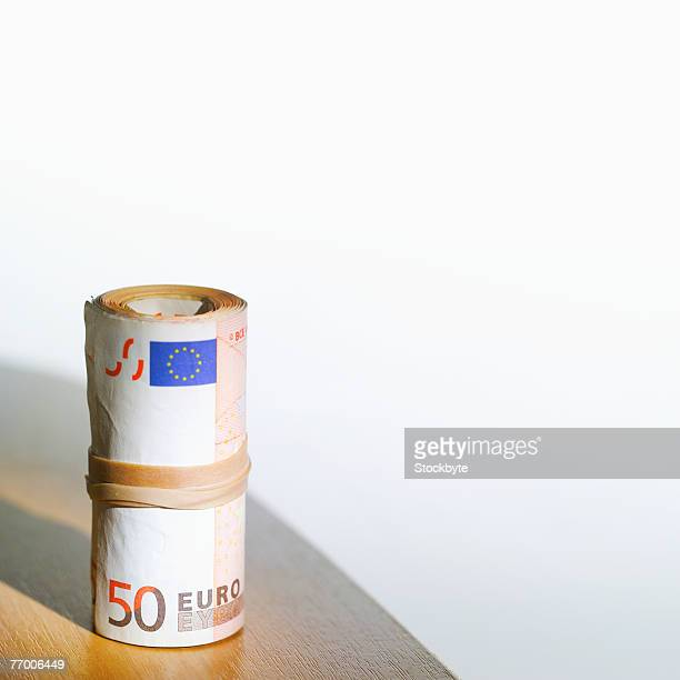 Roll of bank of notes on table