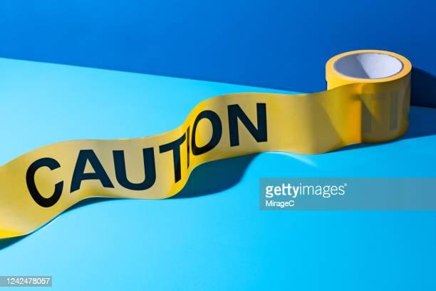 a roll of caution tape - farbquadrat stock-fotos und bilder