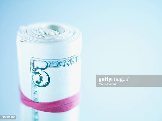 Roll of five dollar bills