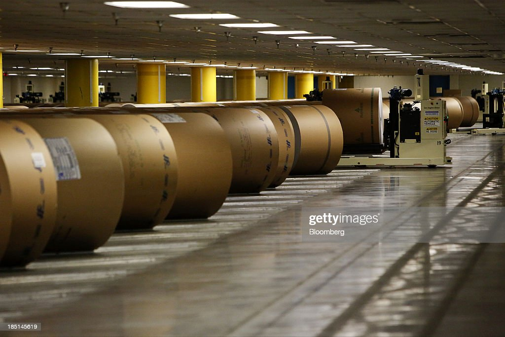 A roll of newsprint is moved by an automatic lift to be loaded into a printing press at the Los Angeles Times Olympic Press facility in Los Angeles, California, U.S, on Wednesday, Oct. 16, 2013. Congress ended the 16-day government shutdown, raising the U.S. debt limit after the leaders of the Senate reached a bipartisan agreement to end the nation's fiscal impasse. Photographer: Patrick T. Fallon/Bloomberg via Getty Images
