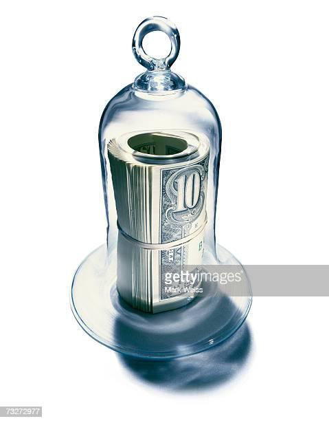 Roll of notes under bell jar