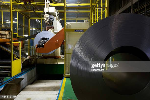 Roll of sheet steel passes through a steel-cutting machine, left, at the Hyundai Motor Co. Factory in Asan, South Korea, on Monday, Jan. 20, 2014....