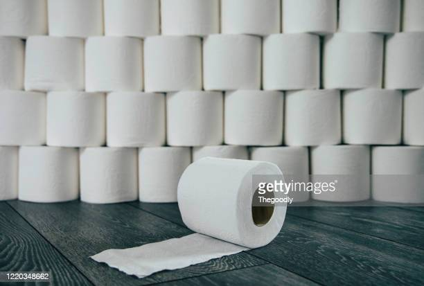 roll of toilet paper in front of a stack of toilet rolls - panic buying stock pictures, royalty-free photos & images