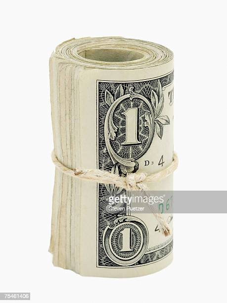 Roll of US dollars tied with string against white background