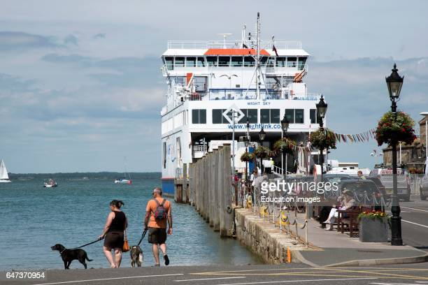 Roll on roll off ferry berthed on the waterfront and passengers walk their pet dogs.
