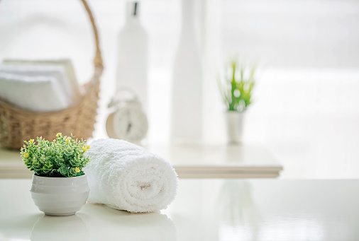 Roll up of white towels on white table with copy space on blurred living room background 985388532