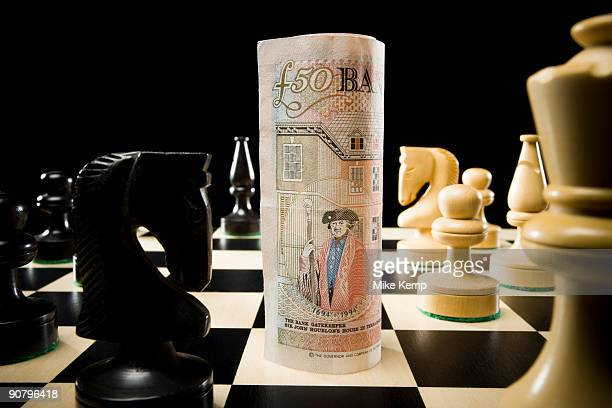rolled currency on a chess board - fifty pound note stock photos and pictures