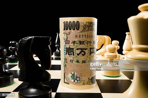 rolled currency on a chess board