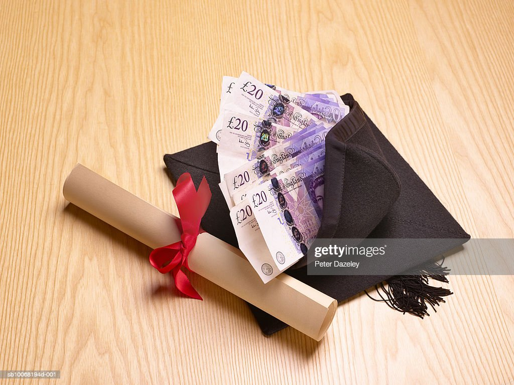 rolled diploma and mortar board twenty pound notes inside  rolled diploma and mortar board twenty pound notes inside studio shot stock photo