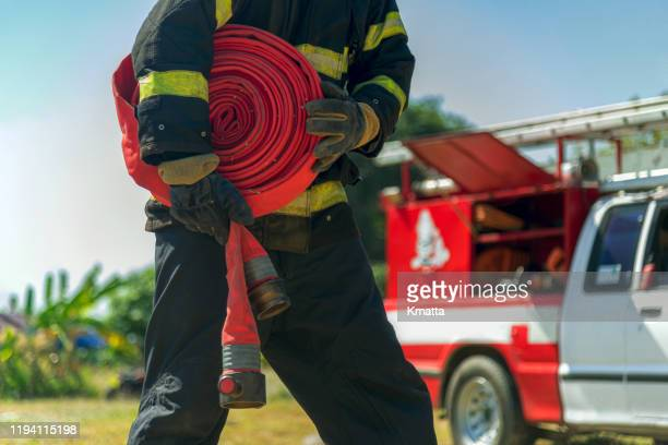 rolled fire hose. - extinguishing stock pictures, royalty-free photos & images