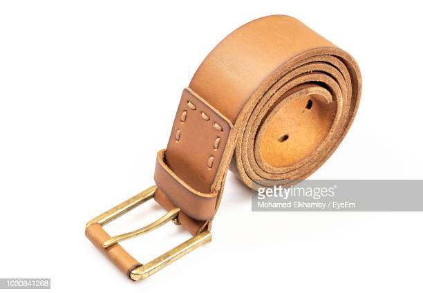 rolled leather belt against white background - leather belt stock pictures, royalty-free photos & images