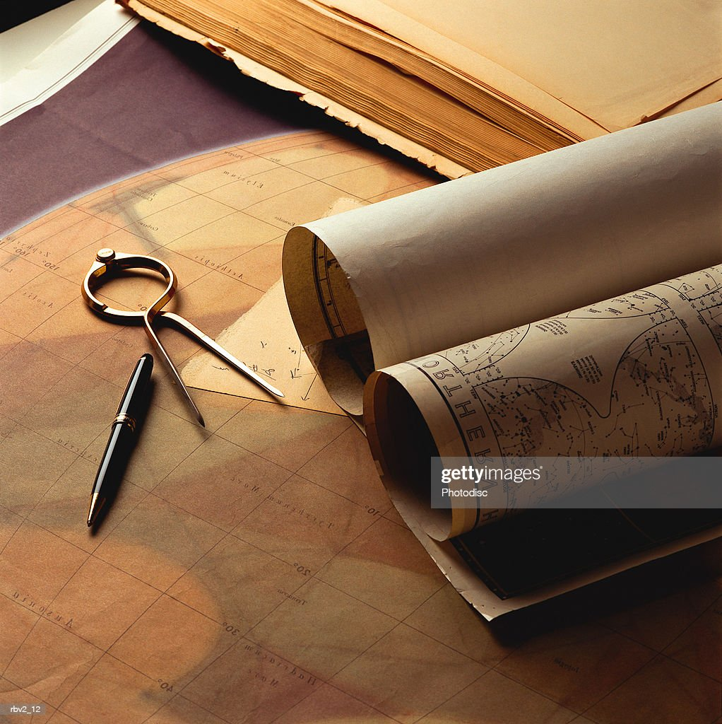 rolled maps and a compass and pen lay on a table with other papers : Foto de stock