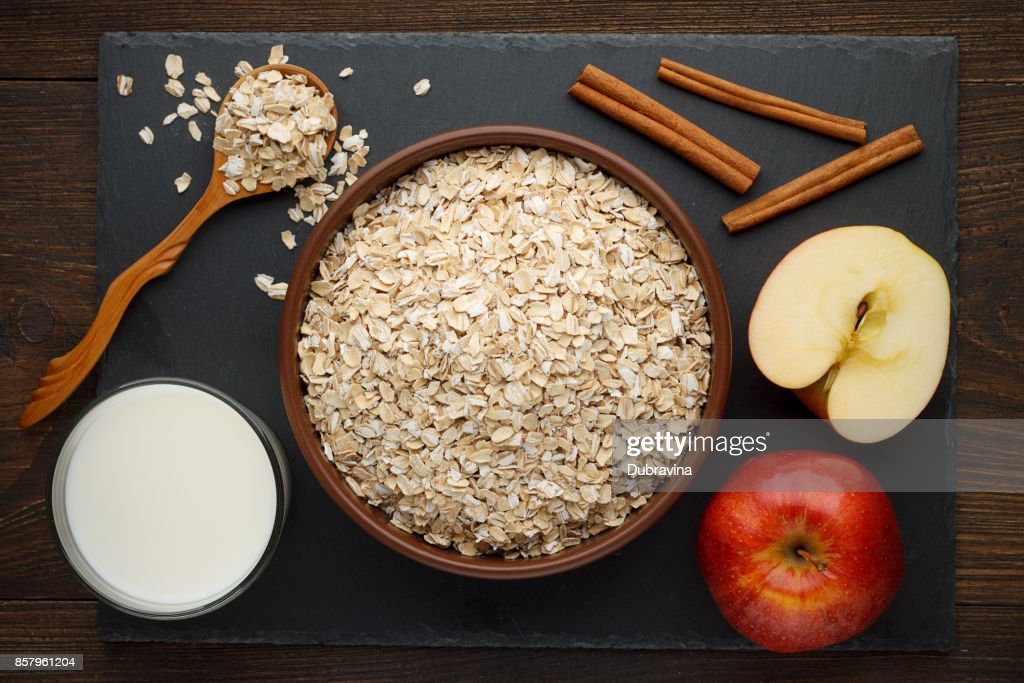 Rolled oat flakes in bowl with apple, cinnamon and milk on slate background. : Stock Photo