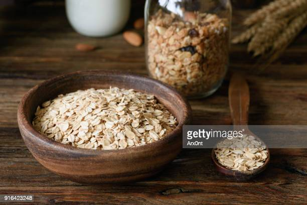Rolled oats and ears of wheat on wooden table