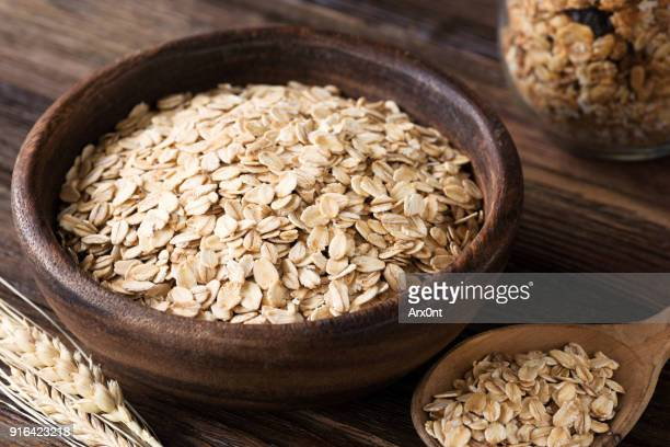 rolled oats and wheat ears on wooden table - rolled oats stock photos and pictures