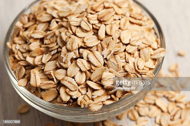 rolled oats in a bowl - oatmeal stock photos and pictures