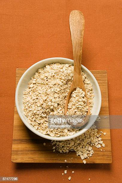 rolled oats in a bowl with wooden spoon - rolled oats stock photos and pictures