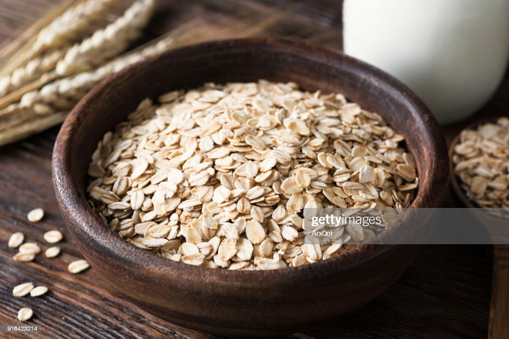 Rolled oats in wooden bowl on old wooden table : Stock Photo