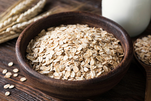 Rolled oats in wooden bowl on old wooden table - gettyimageskorea