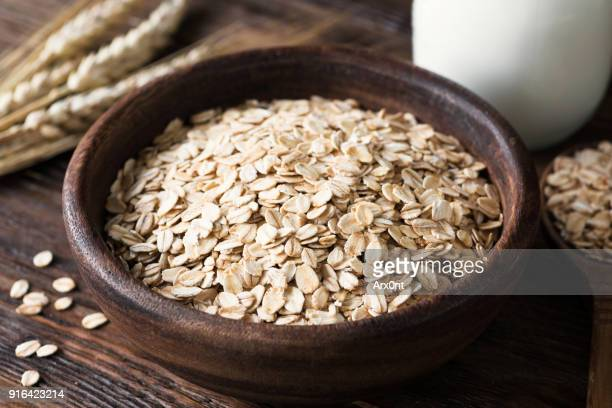 Rolled oats in wooden bowl on old wooden table
