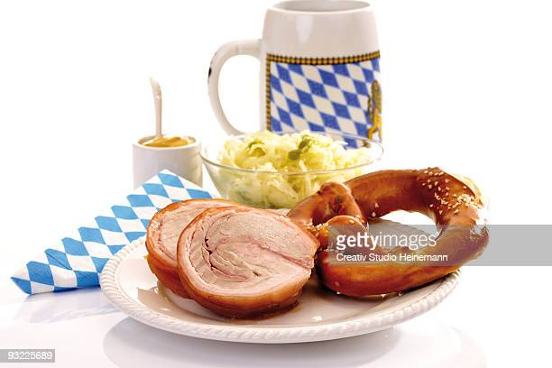 Rolled pig roast, pretzel and cabbage salad with drink, close-up