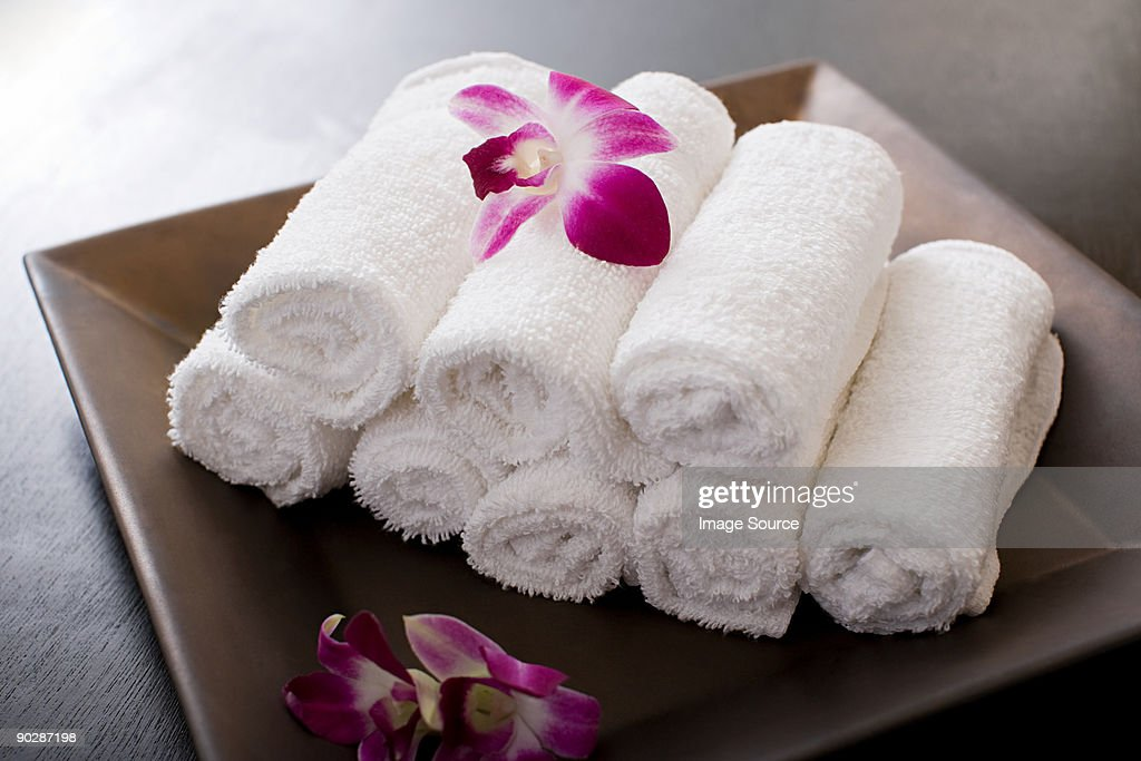 Rolled towels and orchid flowers : Stock Photo