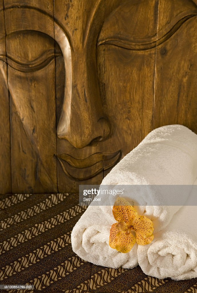 Rolled towels on batik cloth in front of carved image of Buddah : Foto stock