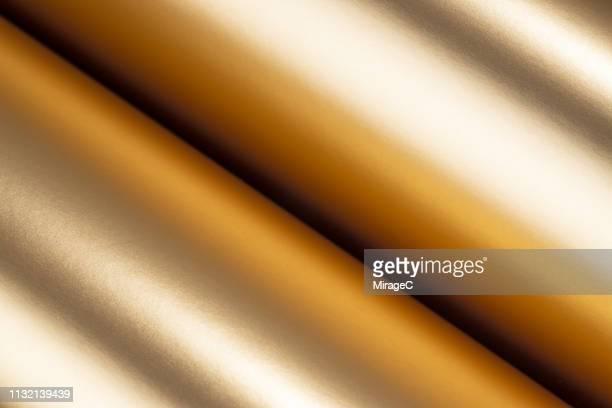 rolled up golden colored texture - metallizzato foto e immagini stock