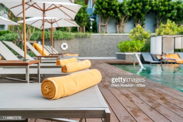 rolled up orange towel on a sun lounger background of pool in re - gazebo stock pictures, royalty-free photos & images